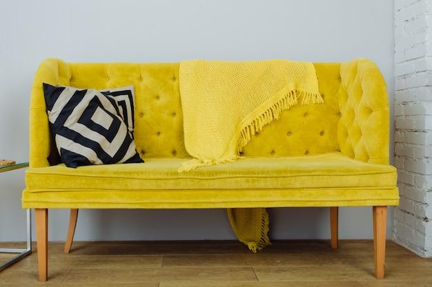 Lindo sofá amarelo com almofadas preto e brancas em uma parede cinza