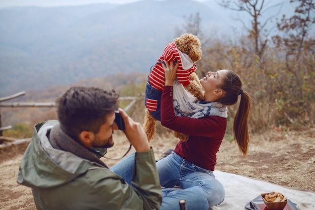 Lindo sorrindo caucasiana morena sentada no cobertor e posando com seu cachorro enquanto o namorado tirando foto deles. piquenique no conceito de outono.