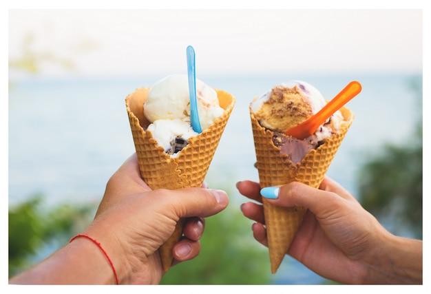 Lindo sorvete brilhante com sabores diferentes nas mãos de um casal