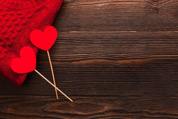 Lindo suéter vermelho e dois corações vermelhos em varas isoladas em um fundo escuro de madeira. vista lateral superior do flatlay. dia dos namorados e conceito de natal. copyspace, moda.