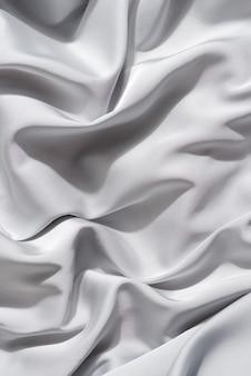 Lindo tecido de seda de delicada cor cinza drapeado com pequenas dobras, fluindo suavemente,