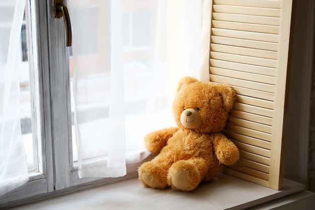Lindo ursinho de pelúcia brinquedo sentado no peitoril da janela