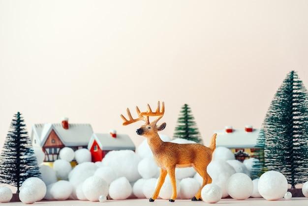 Lindo veado na véspera de natal no fundo de casas rurais, maquete de natal