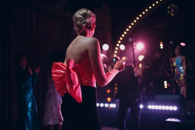Lindo vestido de festa com grande laço de cetim rosa na mulher no clube noturno.