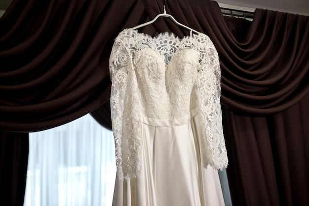 Lindo vestido de noiva pendurado no quarto, mulher se preparando antes da cerimônia