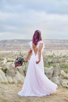 Lindo vestido longo branco no corpo da mulher. noiva perfeita com dança de cabelo rosa. mulher com um lindo buquê de flores nas mãos dela dança na montanha nos raios do pôr do sol do amanhecer