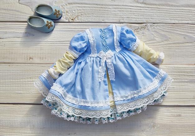 Lindo vestido vintage para uma boneca em uma madeira branca.