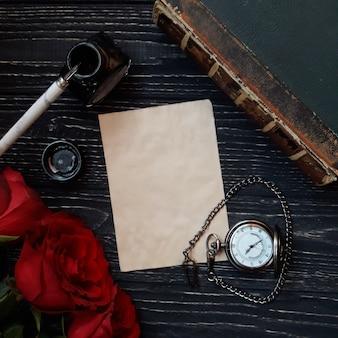Lindo vintage flat-lay com papel, rosas e um relógio