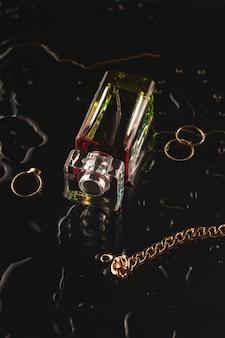 Lindos acessórios e perfume feminino em um fundo preto entre a água