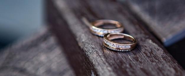 Lindos anéis de casamento com diamantes repousam sobre uma superfície de madeira