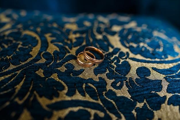 Lindos anéis de ouro sobre uma almofada azul com um padrão.