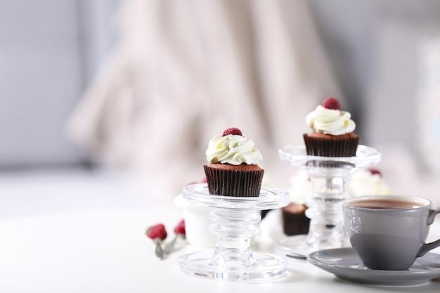 Lindos bolinhos de chocolate com creme e framboesa na mesa