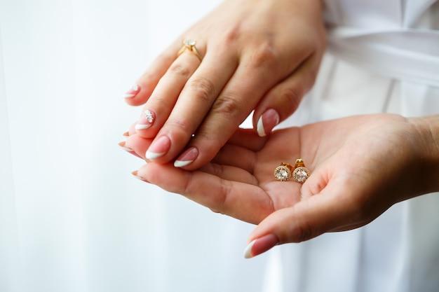 Lindos brincos de casamento nas mãos da noiva no dia do casamento