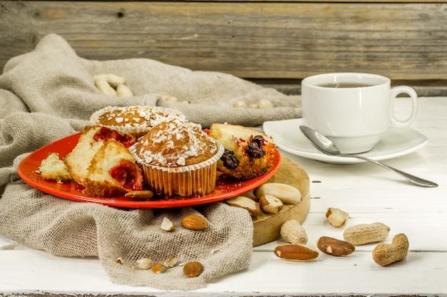 Lindos cupcakes com frutas no fundo de madeira em placa vermelha