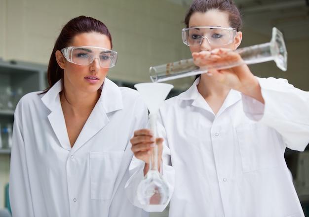 Lindos estudantes de ciências que fazem um experimento