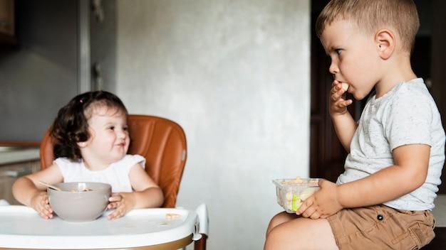 Lindos filhos comendo e olhando um ao outro