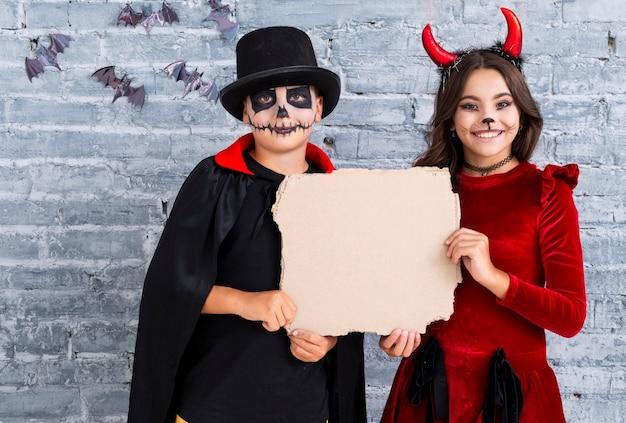 Lindos filhos em trajes de halloween com maquete