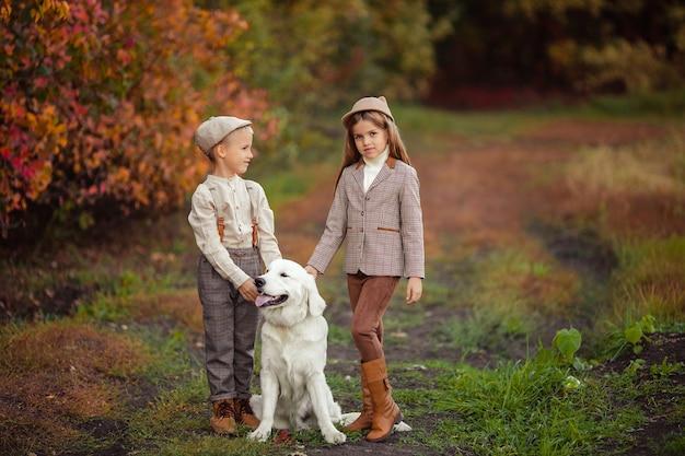 Lindos filhos felizes, irmão e irmã, passeando com seu cachorro retriever