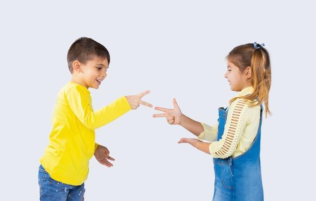 Lindos filhos jogam pedra, tesoura de papel e se divertem em um fundo branco.