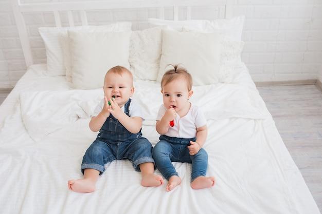 Lindos filhos, menino e menina, sentados na cama com escovas de dente