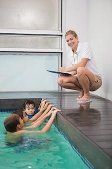 Lindos filhos na piscina ouvindo o treinador