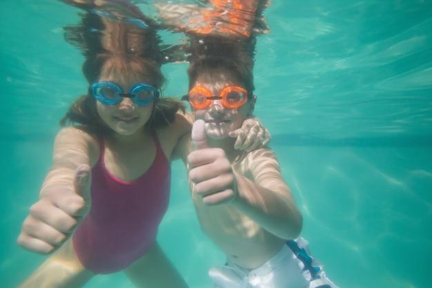 Lindos filhos posando debaixo d'água na piscina no centro de lazer