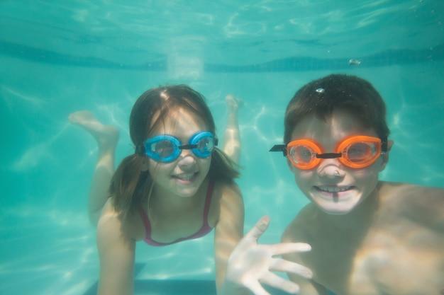Lindos filhos posando debaixo d'água na piscina