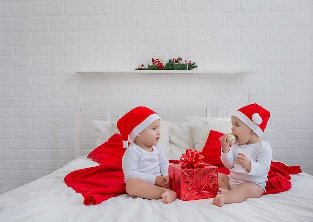 Lindos filhos, um menino e uma menina estão sentados na cama usando chapéus de natal