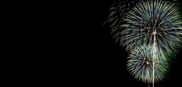 Lindos fogos de artifício coloridos abstratos para celebração em fundo preto com espaço livre para texto