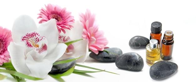 Lindos frascos de orquídeas e óleos essenciais com pedras pretas