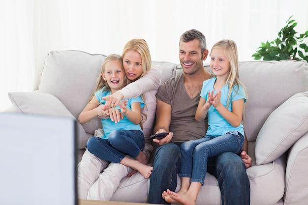 Lindos gêmeos e pais assistindo televisão