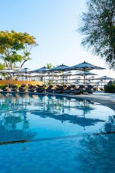 Lindos guarda-sóis e cadeiras de luxo ao redor da piscina ao ar livre