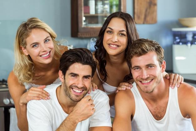Lindos jovens casais sorrindo em casa