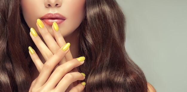 Lindos lábios perfeitamente formados, coloridos por batom rosa atrás de dedos delgados com manicure amarela nas unhas. cabelo denso em volta dos detalhes do rosto da mulher.