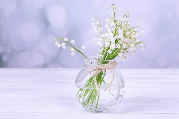 Lindos lírios do vale em um vaso de vidro na mesa de madeira