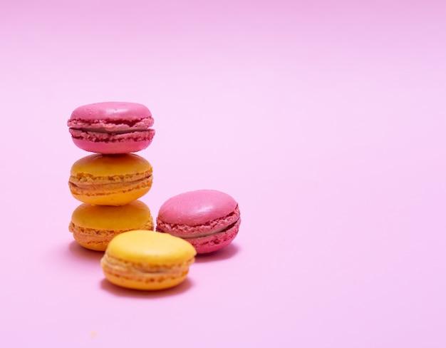 Lindos macarons rosa e amarelos empilhados uns sobre os outros em um fundo rosa