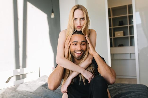 Lindos momentos engraçados de casal fofo se divertindo na cama em casa em um apartamento moderno. cabelo loiro comprido, emoções verdadeiras, zangado, feliz, amor, esposa, marido, relacionamento