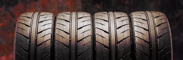 Lindos novos pneus de verão com um padrão de piso direcional para corridas de automóveis e automobilismo. fundo de fogo avermelhado.