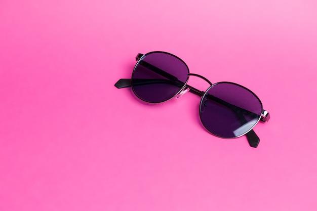 Lindos óculos de sol em close-up de fundo rosa isolado