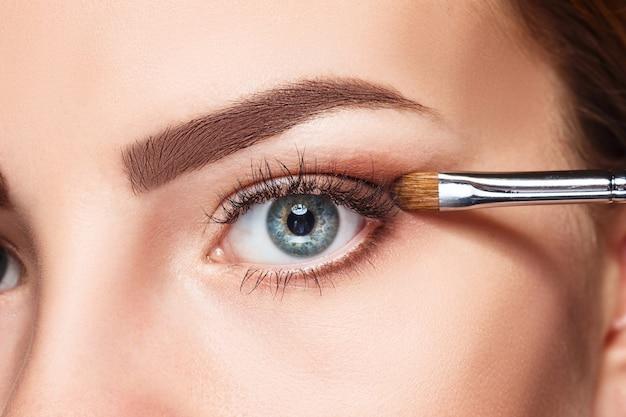 Lindos olhos femininos com maquiagem e pincel no branco