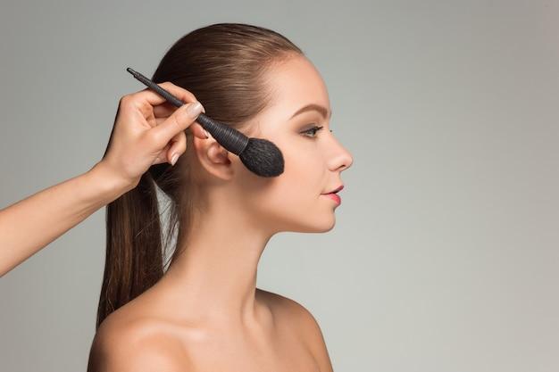 Lindos olhos femininos com maquiagem e pincel
