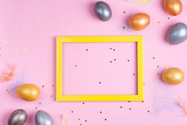 Lindos ovos de prata e ouro da páscoa com moldura amarela em fundo de estrelas rosa