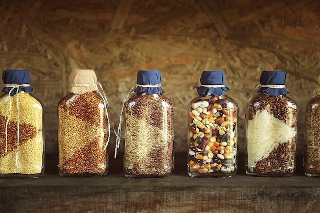 Lindos potes com grãos, cereais, leguminosas e sementes na mesa de madeira