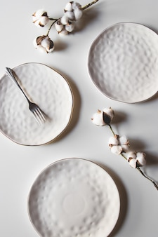 Lindos pratos em um fundo branco com algodão. layout bonito