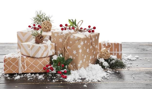 Lindos presentes de natal em uma mesa de madeira contra uma superfície branca