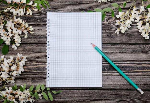 Lindos ramos de acácia em flor e bloco de notas com lápis