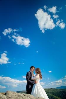 Lindos recém-casados abraçando contra o pano de fundo de rochas e montanhas. noiva elegante e linda noiva estão de pé no penhasco.