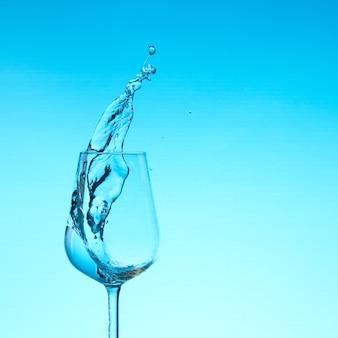 Lindos salpicos de água em uma taça de vinho, com filtro azul, fechem com espaço de cópia.