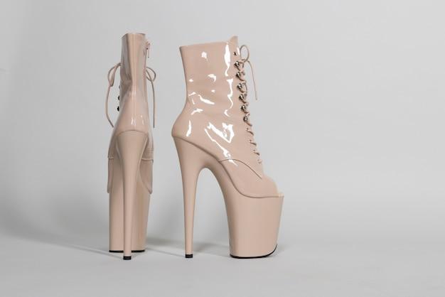 Lindos sapatos bege brilhantes para pole dance ou striptease em um fundo cinza