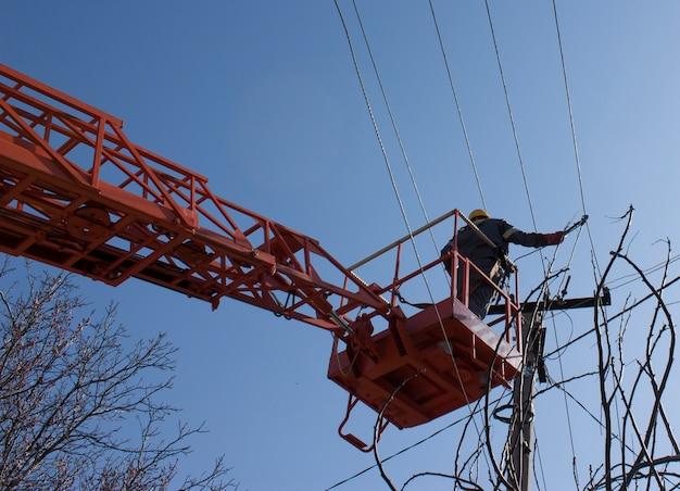Lineman duty working fix power line em cabo elétrico com plataformas de trabalho aéreo